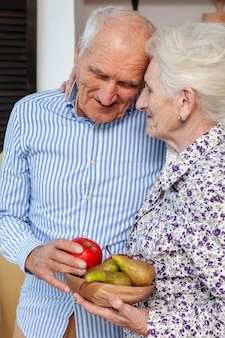 Portrait of mature couple holding fruits