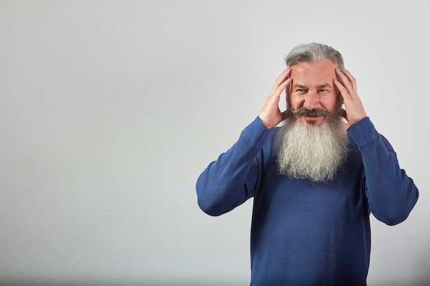 Portrait of mature gray-haired bearded man in blue sweatshirt with a headache