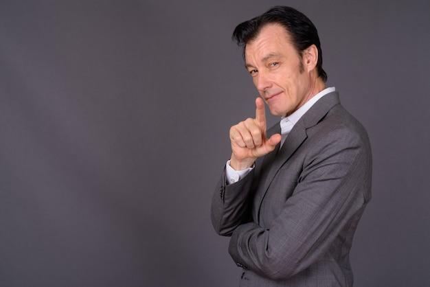 Portrait of mature handsome businessman against gray