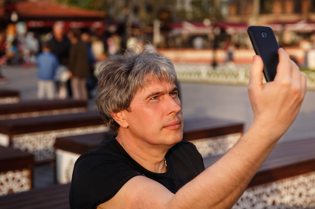Portrait of mature handsome man looking at mobile phone. serious adult man with grey hair. senior man makes selfie with smart phone