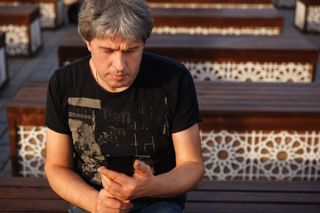 Portrait of mature handsome man looking at mobile phone. serious adult man with grey hair. senior man with smartphone