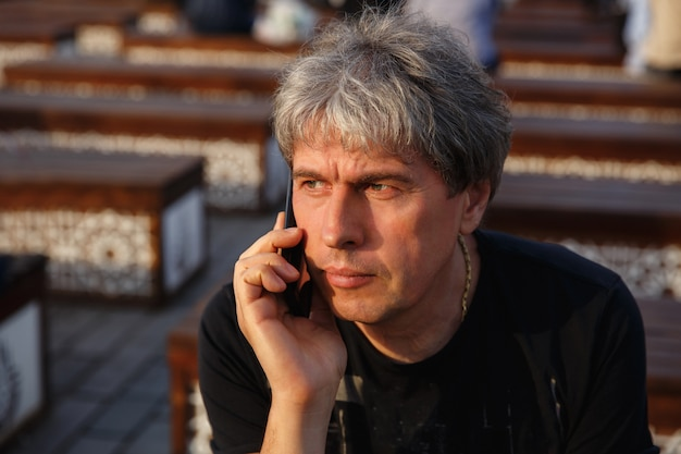 Portrait of mature handsome man talking on smartphone. serious adult man with grey hair. senior man with smartphone