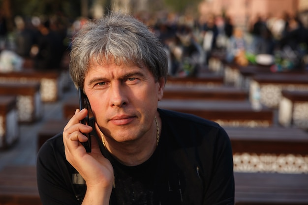 Portrait of mature handsome man with smartphone looking at camera. serious adult man with grey hair. senior man with mobile phone