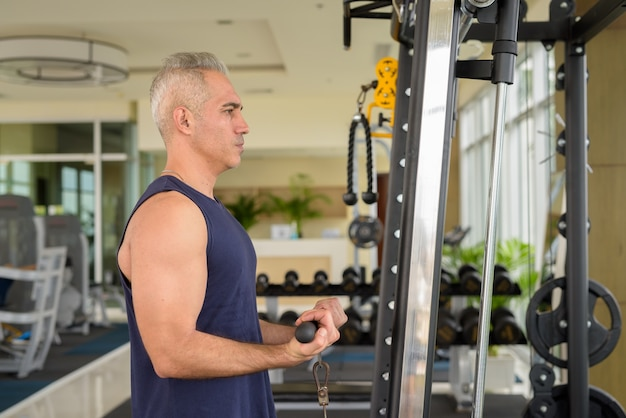 Portrait of mature handsome persian man with gray hair exercising at the gym