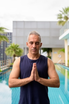 Portrait of mature handsome persian man with gray hair relaxing at the swimming pool on rooftop