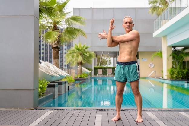 Portrait of mature handsome persian man with gray hair shirtless at the swimming pool on rooftop
