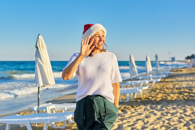 Portrait of mature happy woman in santa hat on the beach sea resort