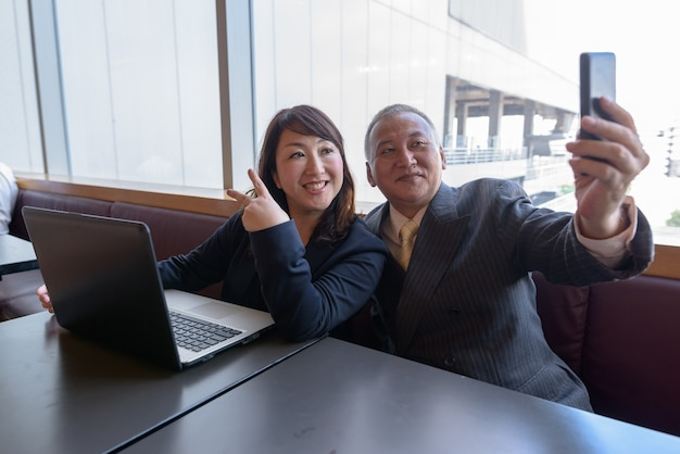Portrait of mature japanese businessman and mature japanese businesswoman relaxing at the restaurant together