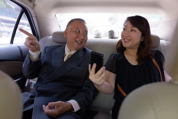Portrait of mature japanese businessman and mature japanese woman exploring the city of bangkok