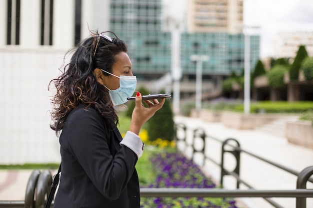 Portrait of mature latin woman with medical mask listening to voice message while walking.