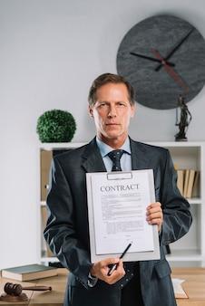 Ritratto dell'avvocato maturo che mostra l'accordo contrattuale legale nell'aula di tribunale