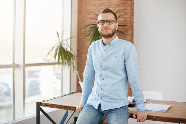 Portrait of mature male freelance designer in glasses and casual clothes, standing in modern co-working space