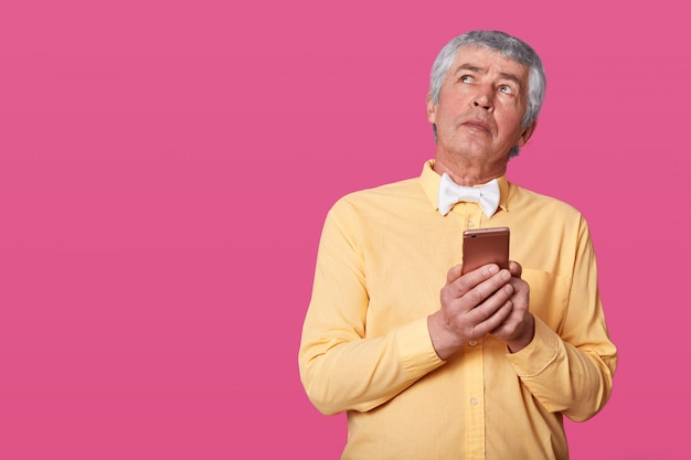 Portrait of mature man having wrinkles and gray hair dressed in yellow shirt and white bow tie, holding smartphone in hands, looks up. elderly man with mobile phone posing in studio isolates on pink.