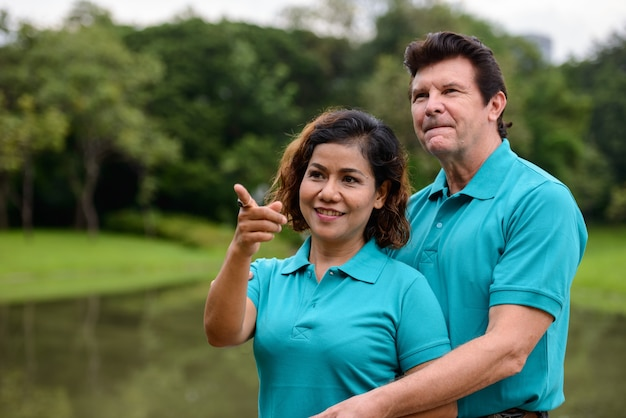 Portrait of mature man and mature asian woman as multi ethnic married couple together and in love at the park outdoors