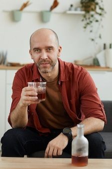 Portrait of mature man sitting on sofa with glass of whiskey. he resting at home