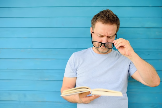 Portrait of mature man with big black eyeglasses trying to read book but having difficulties seeing text