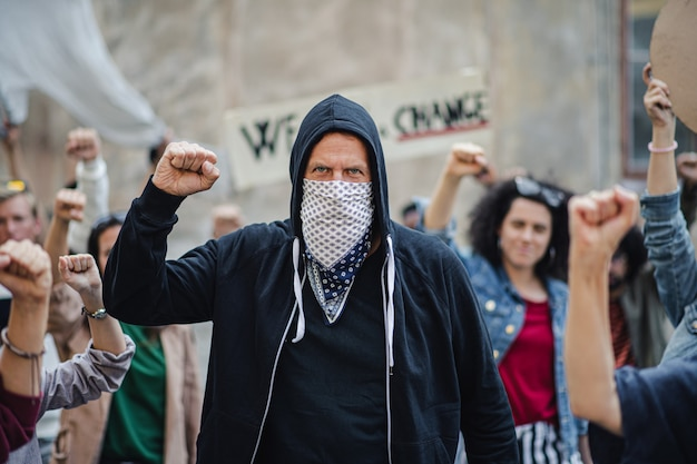Portrait of mature man with group of people activists protesting on streets demonstration