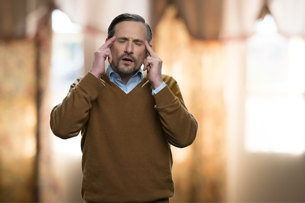 Portrait of mature man with headache. massaging temples. blurred interior on the background.