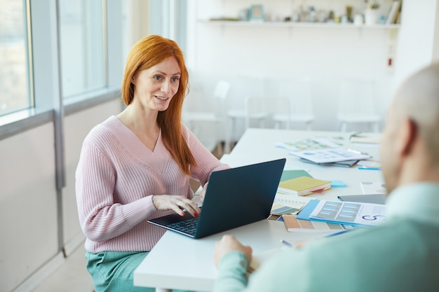 Portrait of mature red haired businesswoman interviewing man while using laptop in office, copy space