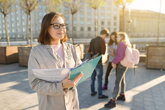 Portrait of mature smiling female teacher in glasses with clipboard
