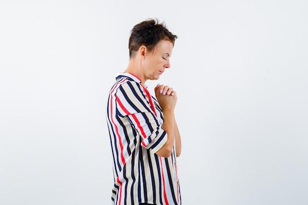 Ritratto di donna matura stringendo le mani nel gesto di preghiera in camicia a righe e guardando speranzoso