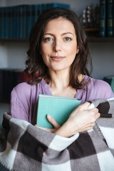 Portrait of a mature woman covered in blanket holding book
