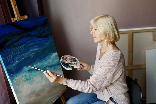 Portrait of mature woman draws with acrylic on canvas