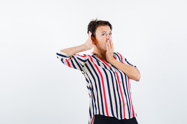 Portrait of mature woman holding hand on mouth while overhearing private conversation in striped shirt and looking surprised front view