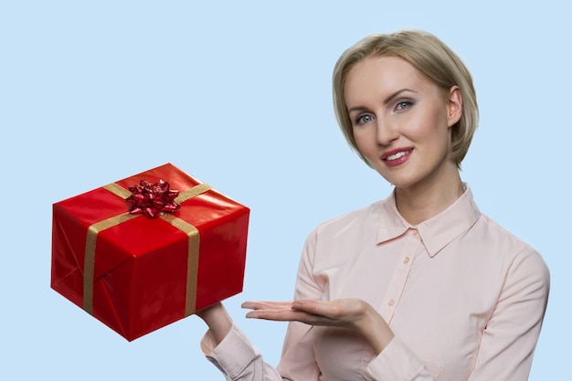 Portrait of mature woman is showing a red gift box