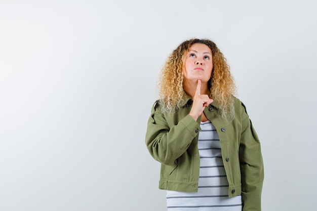 Portrait of mature woman keeping finger under chin while looking up in green jacket, t-shirt and looking curious front view