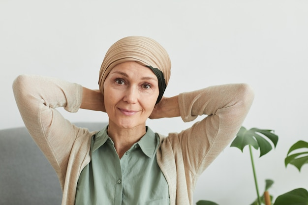 Portrait of mature woman looking at camera while putting on headscarf at home and getting ready to go out, copy space