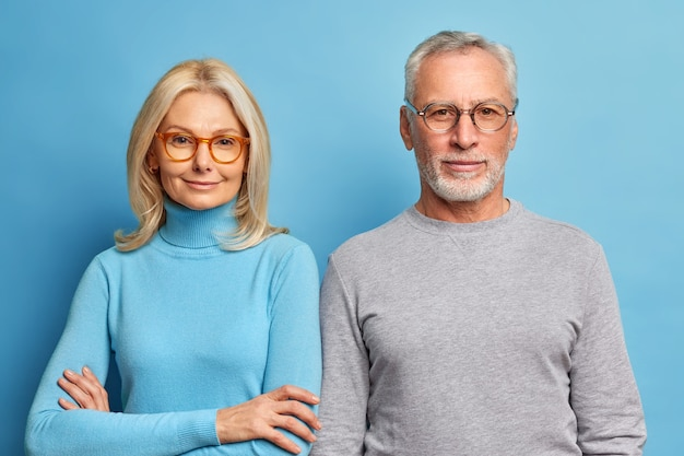 Portrait of mature woman and man stand next to each other in casual clothes against blue wall look directly at front with calm expressions