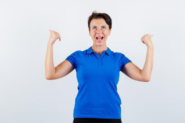 Ritratto di donna matura che punta indietro con i pollici in maglietta blu e guardando fiducioso vista frontale