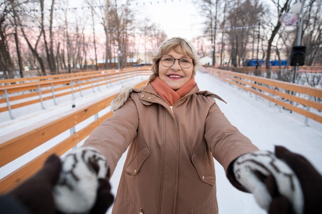 Portrait of mature woman smiling at camera and holding hands of her husband during their ride on skating rink