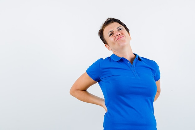 Portrait of mature woman suffering from backache in blue t-shirt and looking uncomfortable front view