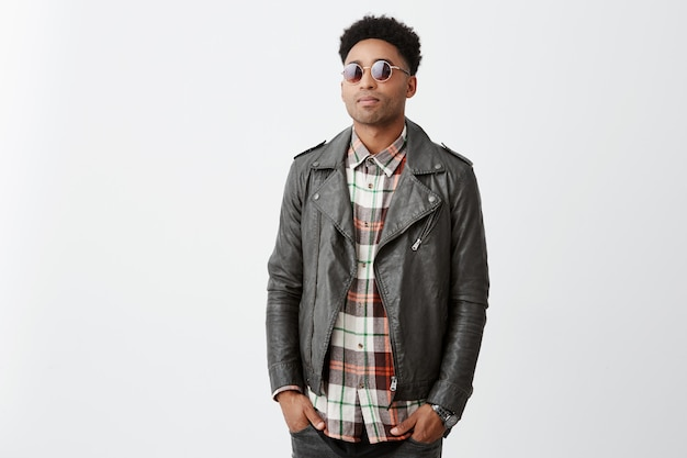 Portrait of mean good-looking dark-skinned guy with afro hairstyle in checkered shirt under leather jacket and sunglasses holding hands in pockets, waiting for girlfriend outside cafe.