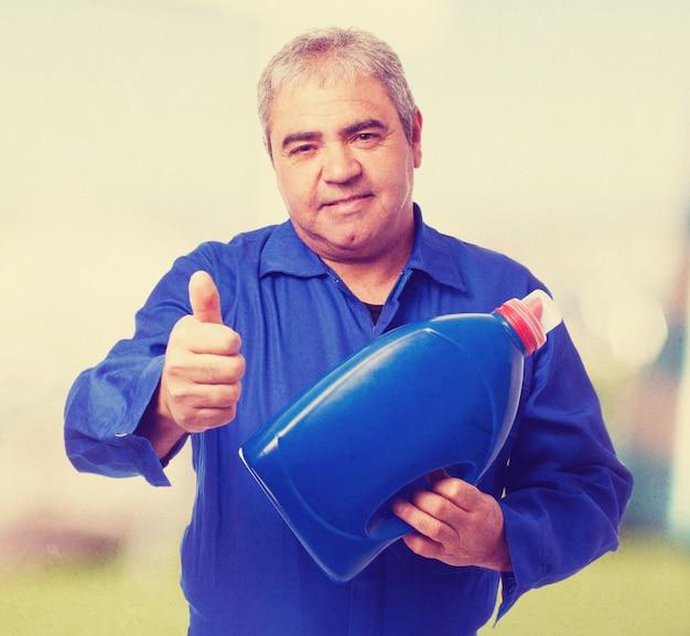 Portrait of a mechanic holding an oil bottle