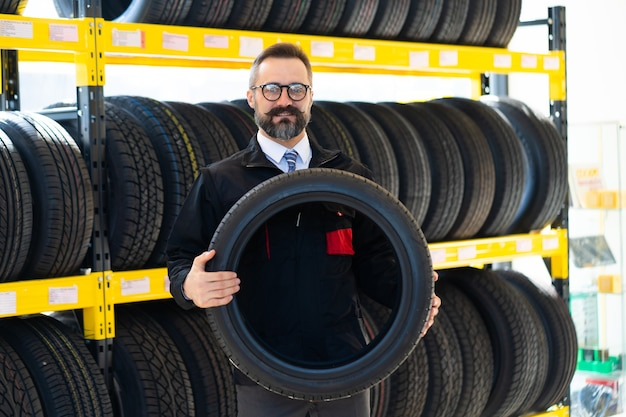 Portrait of mechanic man with car tires at service station. male mechanic holding car tire in automobile store shop