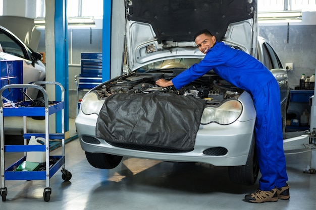 Portrait of mechanic servicing car engine