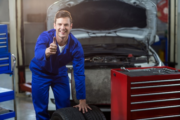 Portrait of mechanic showing thumbs up