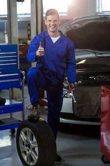 Portrait of mechanic showing thumbs up