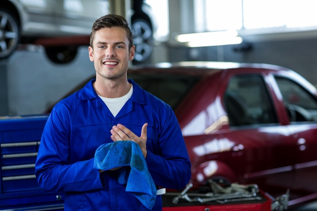 Portrait of mechanic wiping hands with cleaning cloth