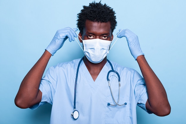 Portrait of medical assistant putting mask on face for protection