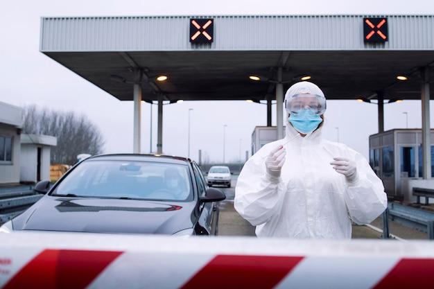 Portrait of medical heath care worker in protective white suit with gloves standing at border crossing and holding test kit for covid-19.