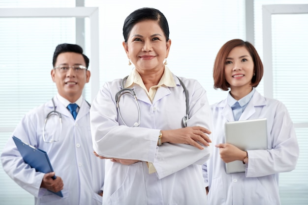 Portrait of medical team of three standing in the hospital looking at camera