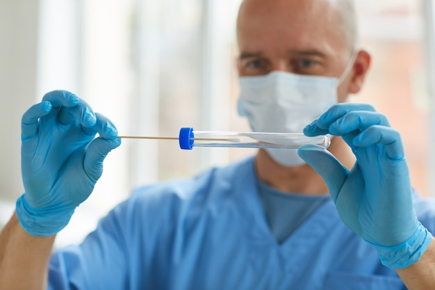 Portrait of medical worker wearing protective mask and gloves putting swab sample into test tube