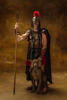Portrait of medieval person warrior in war equipment isolated on vintage dark