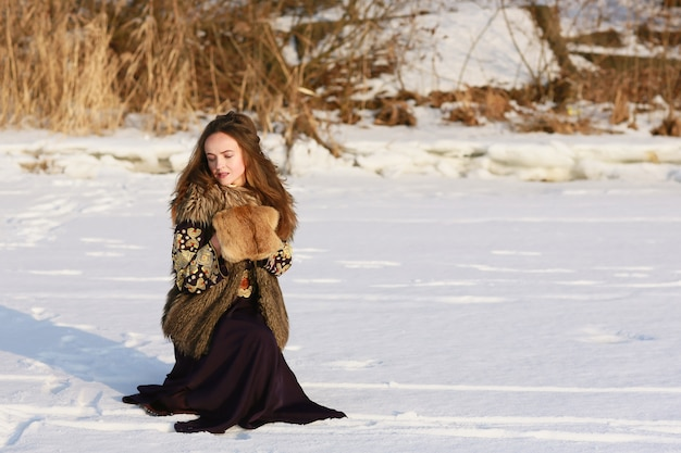 Portrait of a medieval viking girl in a long dress in the winter