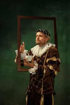 Portrait of medieval young man in vintage clothing with wooden frame on dark wall