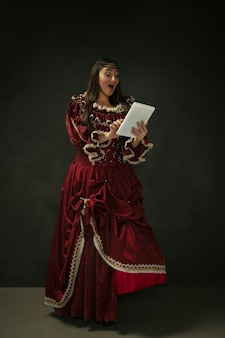 Portrait of medieval young woman in red vintage clothing using tablet on dark background.